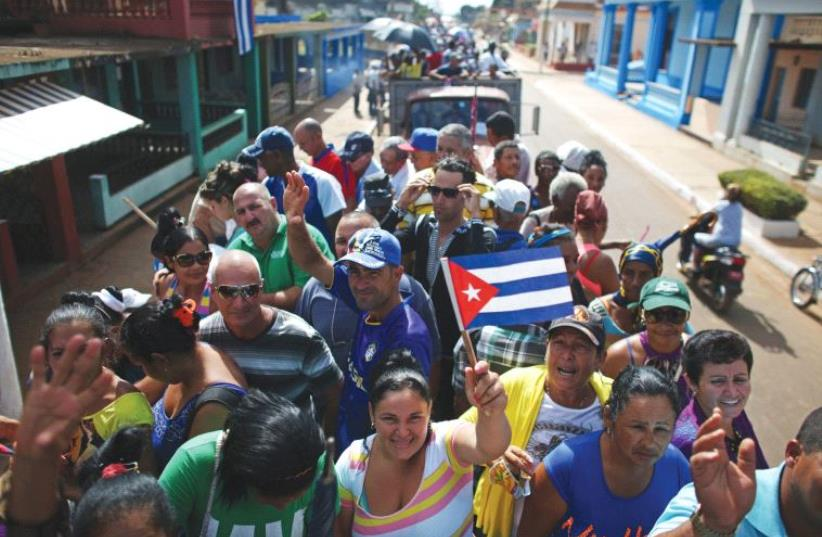 PEOPLE ARE transported to greet the caravan carrying the ashes of Fidel Castro in Colon, Cuba, on Wednesday. (photo credit: REUTERS)
