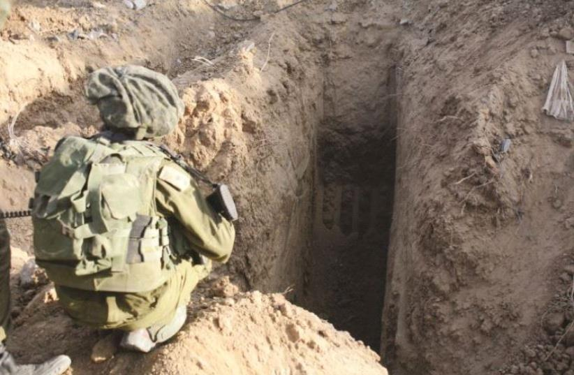 IDF soldier next to a Hamas tunnel (photo credit: IDF SPOKESMAN'S UNIT)