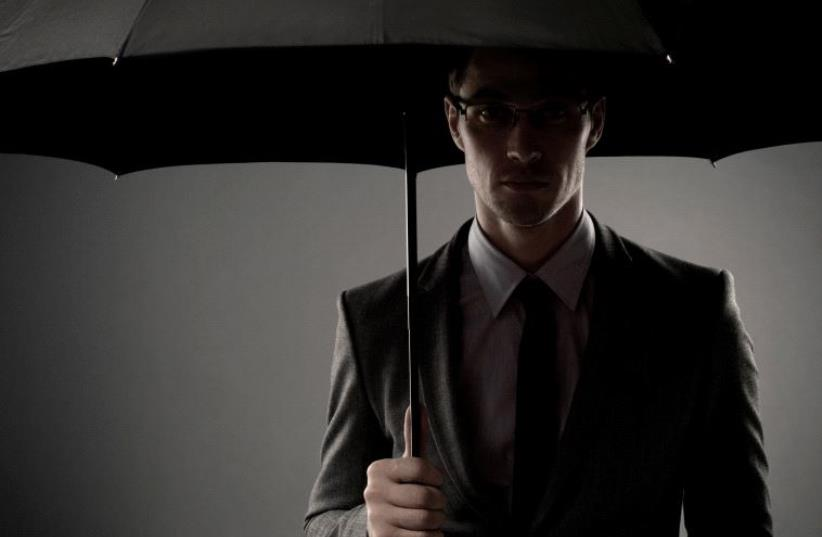 A mysterious man in a black suit standing in the shadows underneath an umbrella, looking like a spy or a secret agent [Illustrative] (photo credit: INGIMAGE)