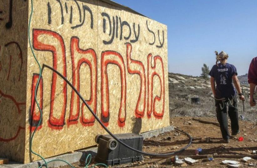 'THERE WILL be war over Amona,' the graffiti reads at the outpost in the Binyamin region of Samaria in the West Bank (photo credit: MARC ISRAEL SELLEM/THE JERUSALEM POST)
