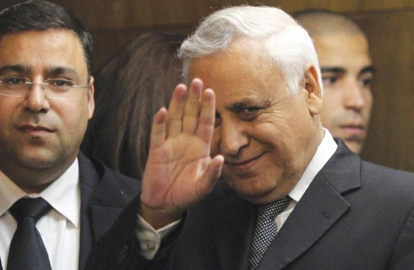FORMER PRESIDENT Moshe Katsav waves to the press as he enters Tel Aviv District Court on December 30, 2010, to hear himself pronounced guilty of rape charges. (photo credit: REUTERS)