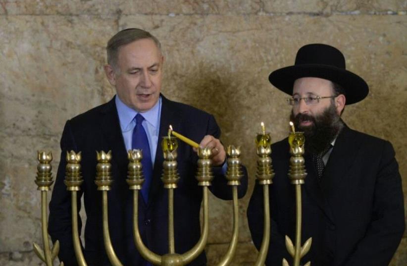 Prime Minister Benjamin Netanyahu Lighting Hanukkah candles at the Kotel (photo credit: AMOS BEN-GERSHOM/GPO)