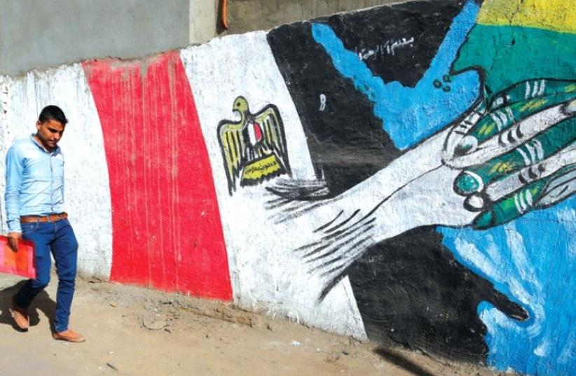 A man walks past graffiti depicting relations between Egypt and Saudi Arabia in Cairo, October 12 (photo credit: REUTERS)