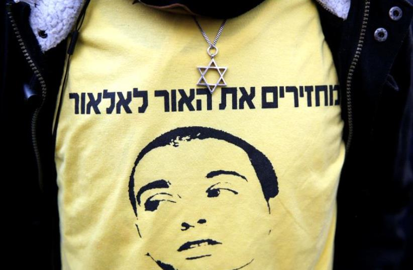 """A supporter of Israeli soldier Elor Azaria, who is charged with manslaughter by the Israeli military, wears a shirt depicting Azaria with the words in Hebrew """"Bringing the light back to Elor"""" during a protest outside the military court in Tel Aviv on the verdict day for the soldier, Tel Aviv, Israel (photo credit: REUTERS)"""