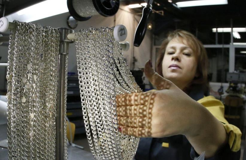 An employee takes silver chains at the jewelry departmen. (photo credit: REUTERS)