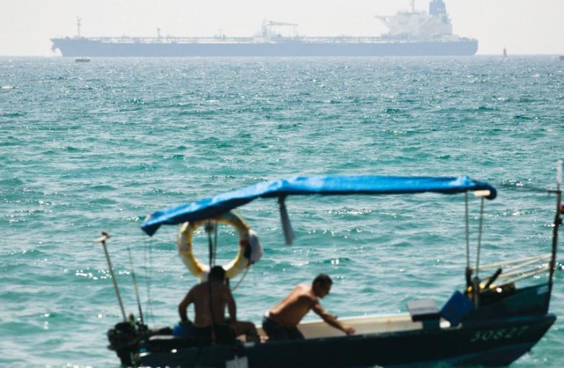 A tanker docks near Israel's Ashkelon port, as men sit in a fishing boat (photo credit: REUTERS)