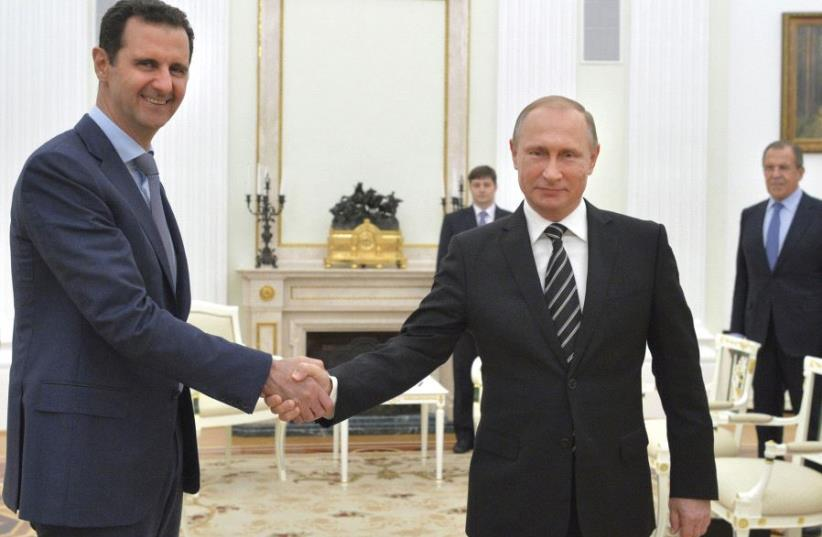 RUSSIAN PRESIDENT Vladimir Putin (right) shakes hands with Syrian President Bashar Assad during a meeting at the Kremlin in Moscow in 2015. (photo credit: REUTERS)