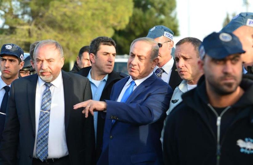 Prime Minister Benjamin Netanyahu (C) and Defense Minister Avigdor Liberman (L) at the scene of a truck-ramming attack in Jerusalem, January 8, 2017 (photo credit: KOBI GIDEON/GPO)