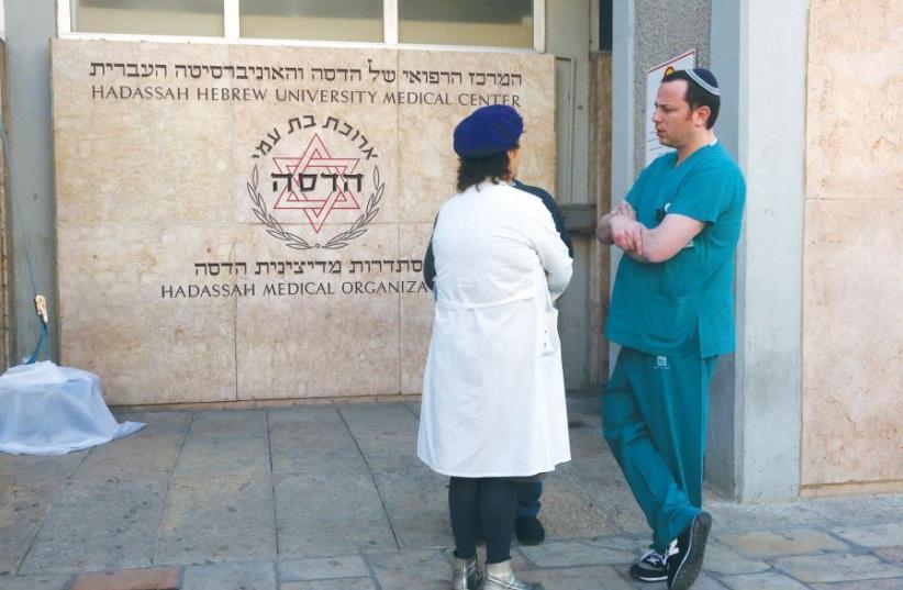 MEDICAL STAFFERS at Jerusalem's Hadassah-University Hospital in Ein Kerem discuss yesterday's call to strike. (photo credit: MARC ISRAEL SELLEM/THE JERUSALEM POST)