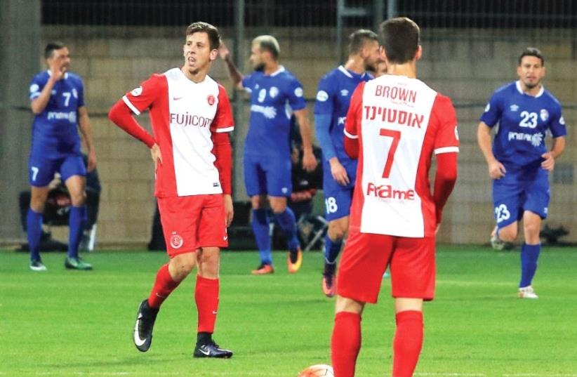 Hapoel Tel Aviv players Ben Reichert (left) and Or Ostvind prepare to renew the game with Ironi Kiryat Shmona players celebrating in the background after taking a 2-0 lead in last night's eventual 2-1 win in Premier League action. (photo credit: ERAN LUF)