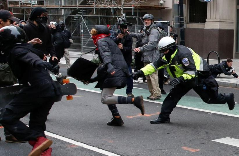 A police officer tries to tackle a protester demonstrating against U.S. President Donald Trump on the sidelines of the inauguration in Washington, DC, US, January 20, 2017. (photo credit: REUTERS)