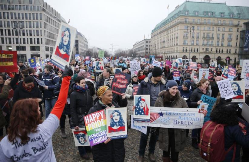 People gather in front of the US Embassy on Pariser Platz beside Brandenburg Gate in solidarity with women's march in Washington and many other marches in several countries, in Berlin, Germany, January 21, 2017.  (photo credit: REUTERS)