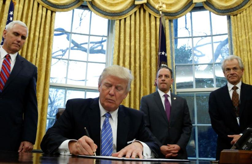 US President Donald Trump signs an executive order in the Oval Office of the White House (photo credit: REUTERS)
