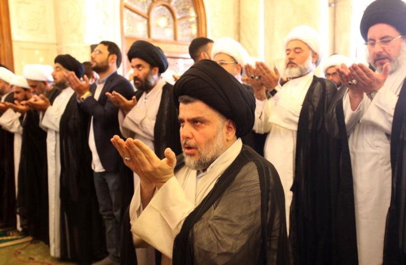Iraqi Shi'ite radical leader Moqtada al-Sadr (C) takes part in Friday prayers at the Kufa mosque near Najaf, Iraq . (photo credit: REUTERS)
