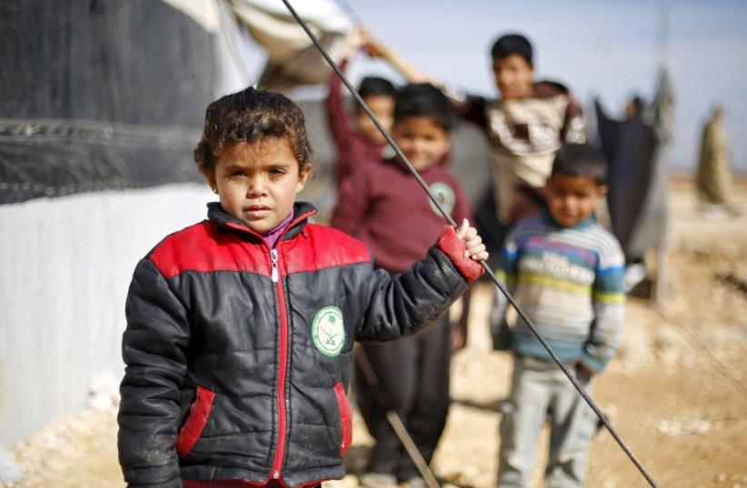 Syrian refugee children pose as they play near their families' residence at Al Zaatari refugee camp in the Jordanian city of Mafraq, near the border with Syria, January 30, 2016. (photo credit: REUTERS)