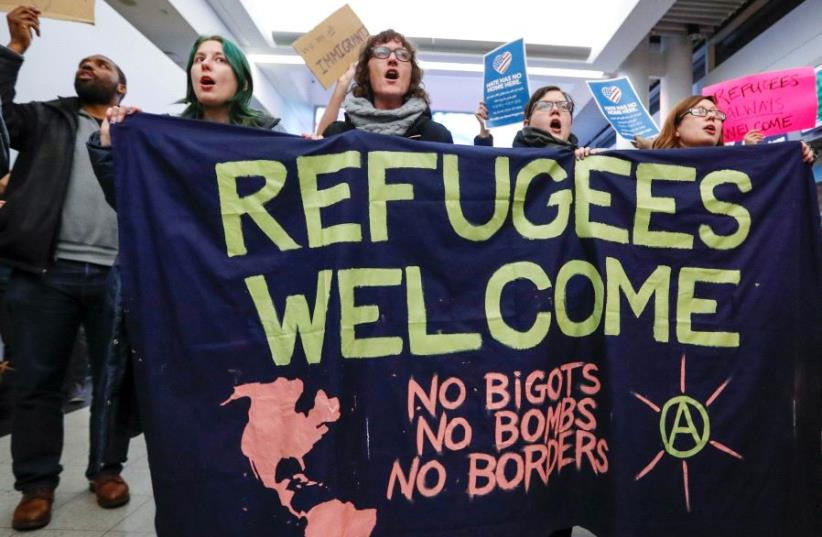 People protest against the travel ban imposed by U.S. President Donald Trump's executive order, at O'Hare airport in Chicago, Illinois, US January 28, 2017.  (photo credit: REUTERS)