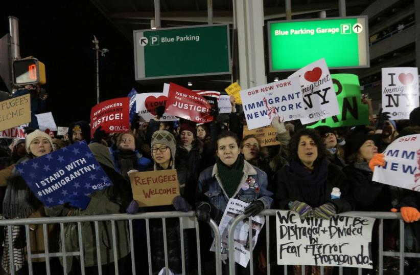Protesters gather outside Terminal 4 at JFK airport in opposition to U.S. president Donald Trump's proposed ban on immigration in Queens, New York City, US, January 28, 2017 (photo credit: REUTERS)