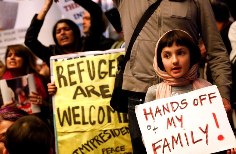 A girl holds a sign in support of Muslim family members as people protest against U.S. President Donald Trump's travel ban on Muslim majority countries. (photo credit: REUTERS)