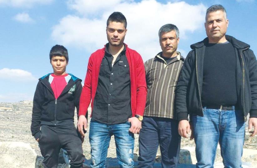 THE AL-AZZEH FAMILY stands yesterday near the ledge where the bus fell in Lubban Sharkiya, south of Nablus. From left: Mahdi al-Azzeh Samih al-Azzeh, Samir al-Azzeh and Jamal al-Azzeh (photo credit: ADAM RASGON)