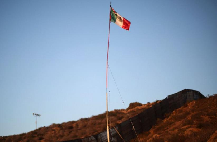 A Mexican flag is seen next to a section of the wall separating Mexico and the United States, in Tijuana, Mexico, October 6, 2016 (photo credit: REUTERS)