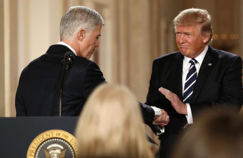 Donald Trump and Neil Gorsuch shake hands (photo credit: REUTERS)