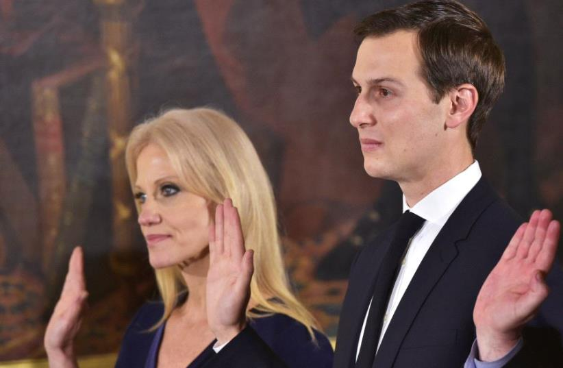 Counselor to the President Kelleyanne Conway (L) and Senior Advisor to the President Jared Kushner raise their hands during the swearing-in of senior staff in the East Room of the White House on January 22, 2017 in Washington, DC (photo credit: MANDEL NGAN/AFP)