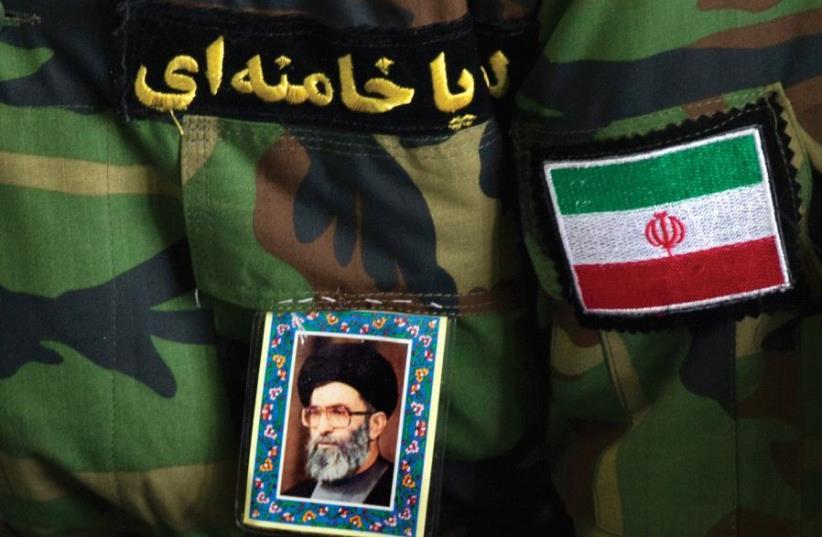 A MAN wearing an Iranian Revolutionary Guard uniform sports a portrait of Iran's Supreme Leader Ayatollah Ali Khamenei. (photo credit: REUTERS)