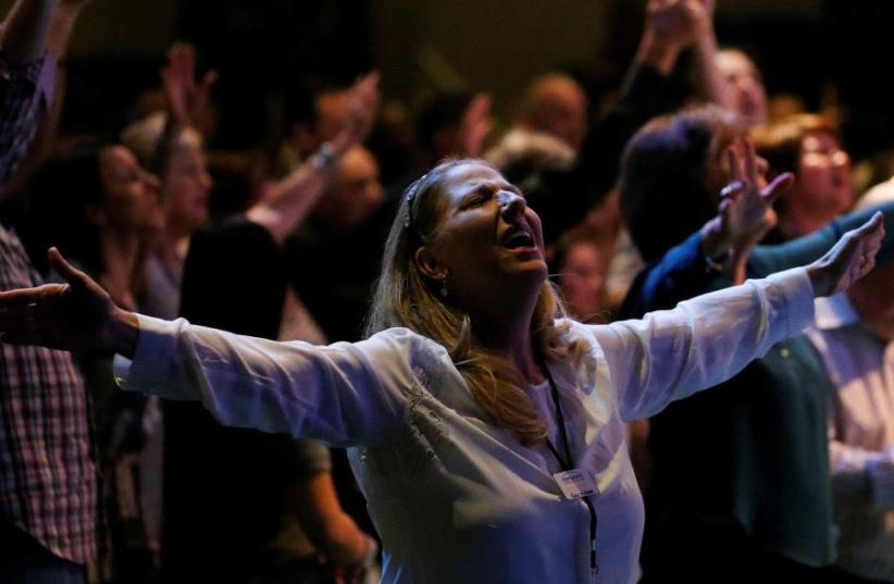A woman prays in the room with then Republican presidential nominee Donald Trump during church service at the International Church of Las Vegas in Las Vegas, Nevada, US October 30 2016. (photo credit: REUTERS)