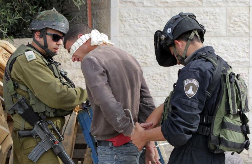 IDF arrest a suspected Palestinian during a raid in Hebron (photo credit: HAZEM BADER / AFP)