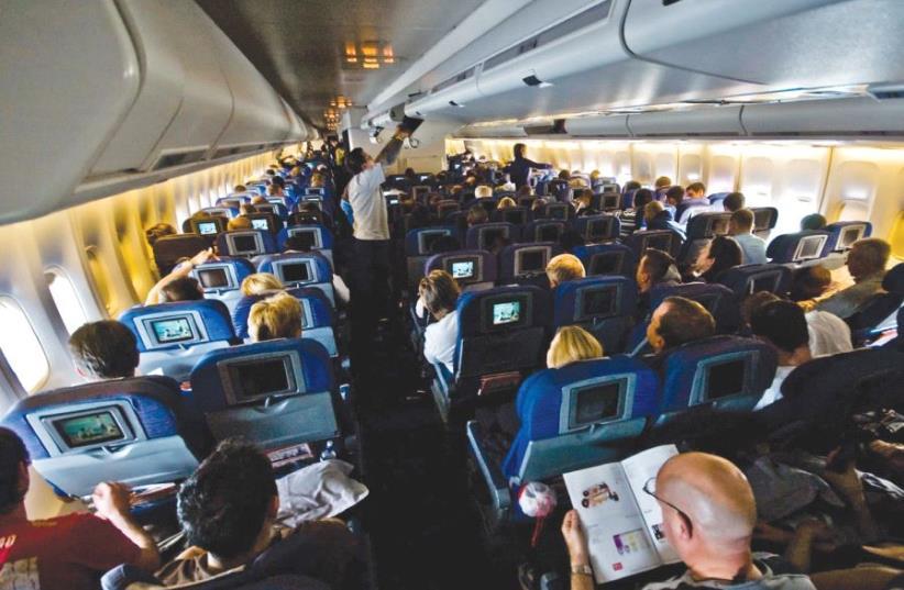 Passengers sitting inside an airplane [illustrative] (photo credit: Wikimedia Commons)