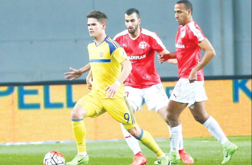 Maccabi Tel Aviv striker Vidar Orn Kjartansson (left) scored the only goal of last night's 1-0 win over Hapoel Beersheba in Netanya, with Maharan Radi (right) and Loai Taha not being able to save their team from defeat (photo credit: DANNY MARON)