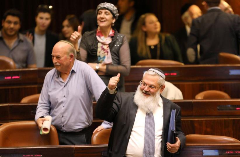 Deputy Defense Minister, Eli Ben-Dahan (front) and other Israeli lawmakers give a thumbs up gesture as they attend a vote on the settlement bill at the Knesset on Feb. 7, 2017 (photo credit: REUTERS)