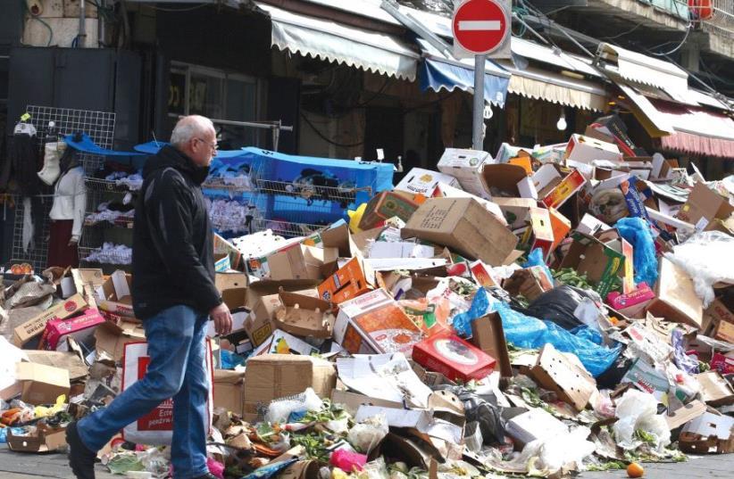 A MAN walks past a heap of garbage outside Jerusalem's Mahaneh Yehuda Market during the three-day municipal strike that began on January 29. (photo credit: MARC ISRAEL SELLEM)