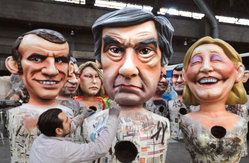 A WORKER puts the final touches on a figure of former French prime minister Francois Fillon, flanked by National Front leader Marine Le Pen and Emmanuel Macron, head of the political movement En Marche!, or Onwards!, during preparations for the carnival parade in Nice, France, earlier this month (photo credit: REUTERS)