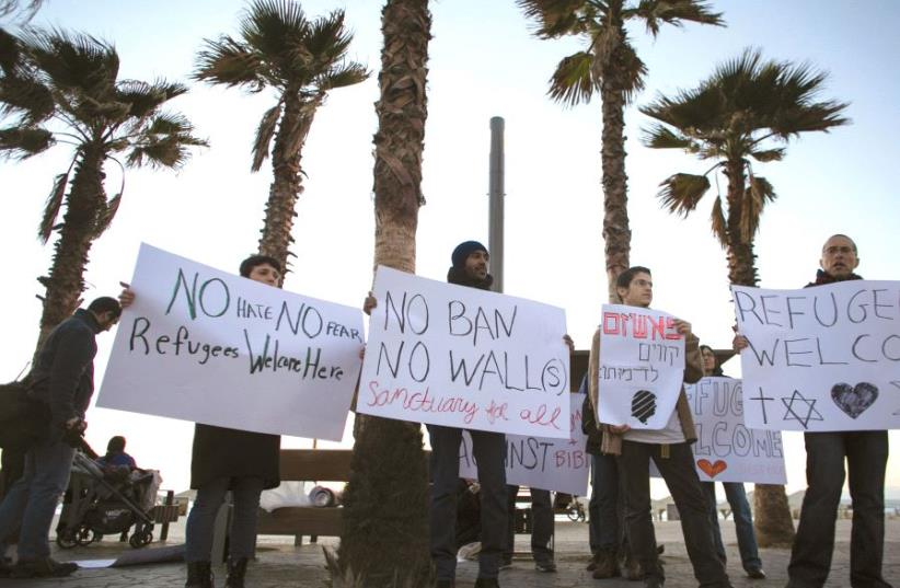 PROTESTERS hold placards during a rally supporting refugees worldwide and in reaction to US President Donald Trump's travel ban outside the US Embassy in Tel Aviv last month (photo credit: REUTERS)