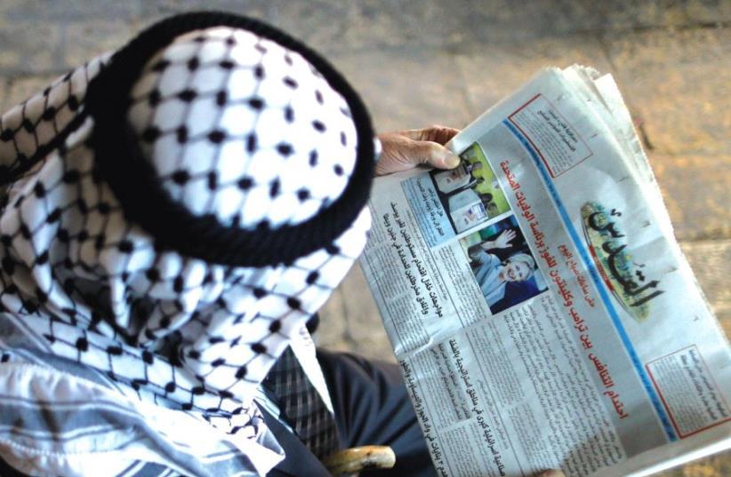 A Palestinian man from Al-Khalil reads 'Al-Quds' newspaper. (photo credit: REUTERS)