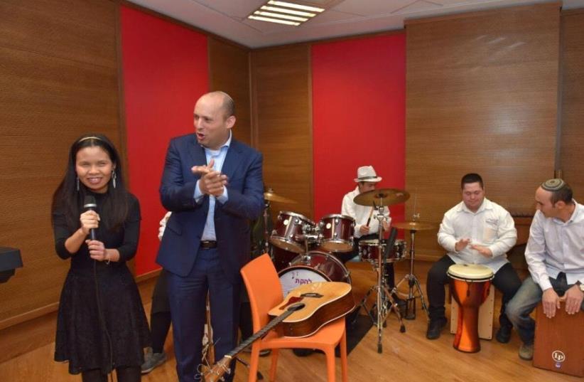 Education Minister Naftali Bennett joins Shalva band on guitar (photo credit: Courtesy)