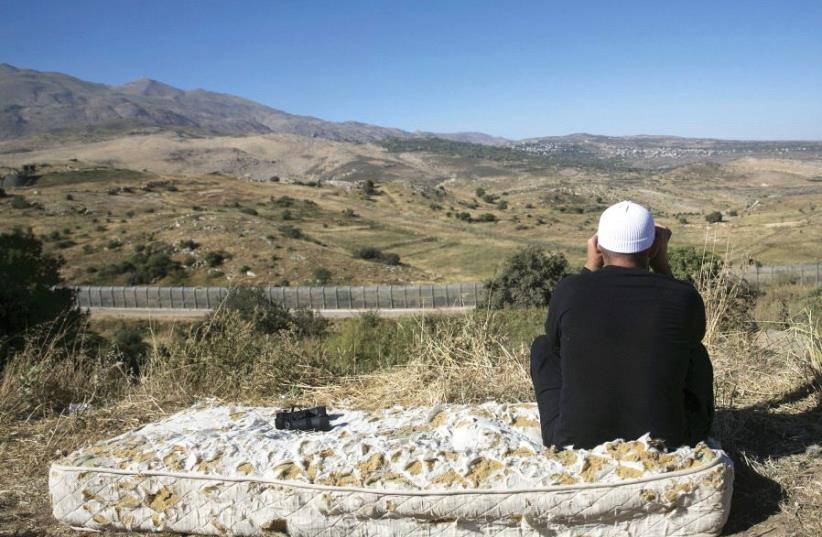 A DRUSE man watches the fighting in Syria from the Israeli side of the Golan Heights (photo credit: REUTERS)