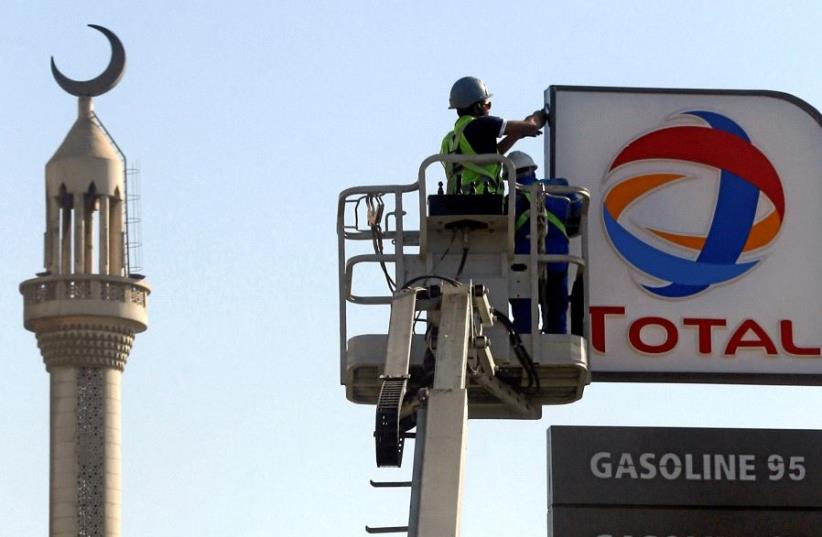 FILE PHOTO: Workers fix a sign for oil giant Total at a petrol station in Cairo, Egypt, October 13, 2016.  (photo credit: REUTERS)