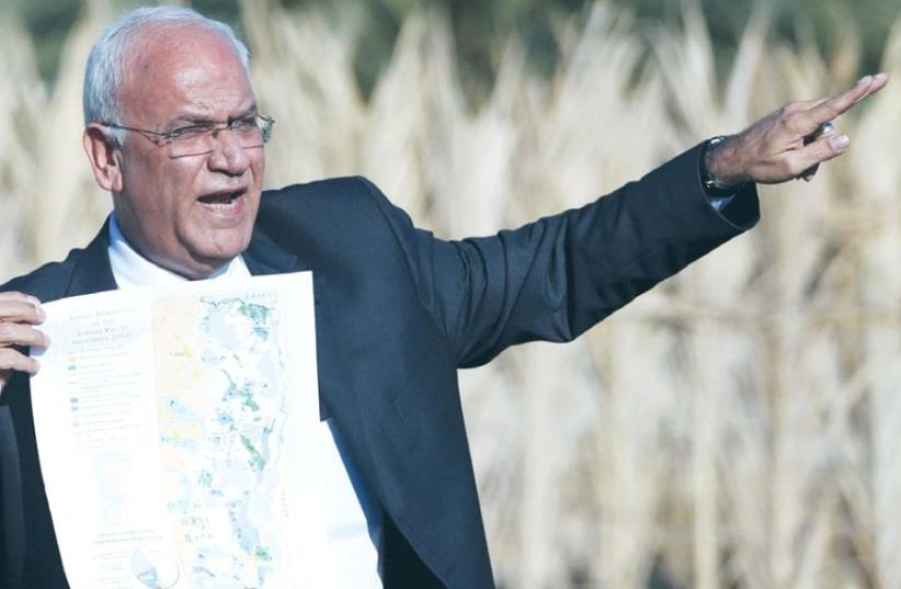 SENIOR PLO OFFICIAL Saeb Erekat speaks to reporters about Israeli appropriation of West Bank land, near Jericho last year. (photo credit: REUTERS)