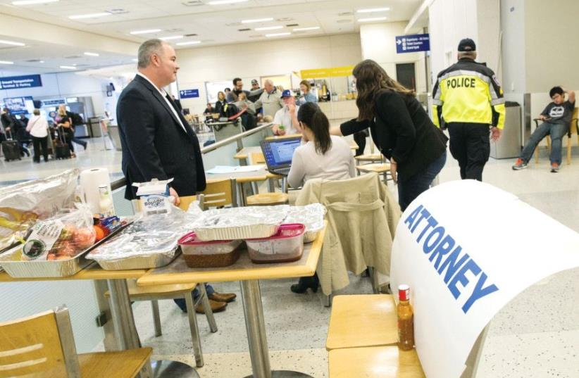Attorneys volunteer their services at Dallas/Fort Worth International Airport, Texas, earlier this month (photo credit: REUTERS)