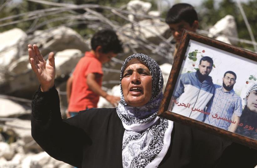 Une mère brandissant la photo de ses enfants, auteurs d'attentats (photo credit: REUTERS)