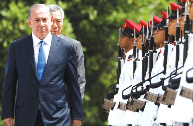 Prime Minister Benjamin Netanyahu inspects an honor guard with Singaporean Prime Minister Lee Hsien Loong at the Istana presidential palace in Singapore. (photo credit: REUTERS)
