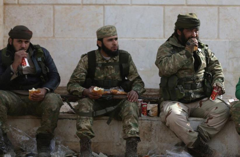 SYRIAN REBEL fighters take a rest during battles around al-Bab in northern Syria (photo credit: REUTERS)