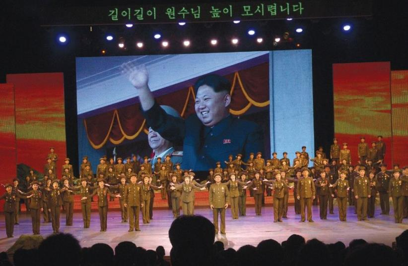 KOREAN DICTATOR Kim Jong-un waves from a giant video screen during a recent military-themed spectacular in Pyongyang. (photo credit: YARIV TAL)
