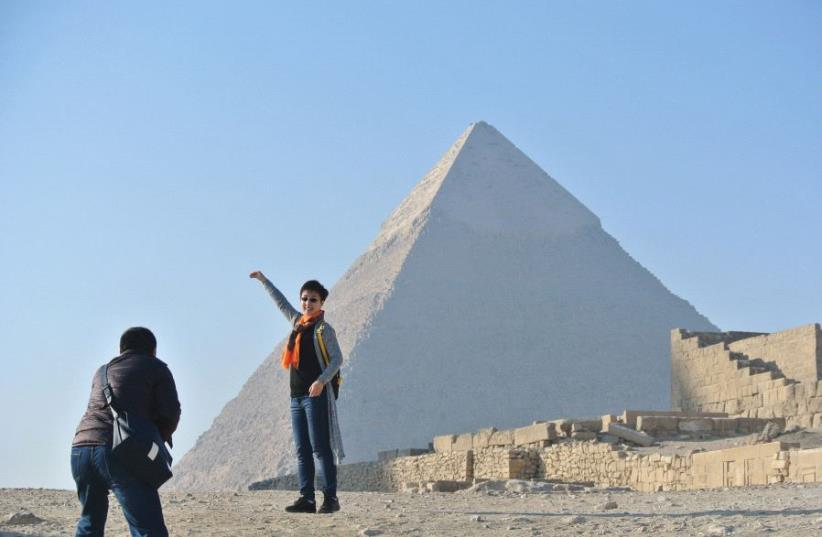 Two tourists pose in front of a pyramid at Giza in Egypt (photo credit: SETH J. FRANTZMAN)