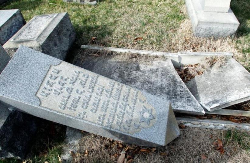 A headstone, pushed off its base by vandals, lays on the ground near a smashed tomb in the Mount Carmel Cemetery, a Jewish cemetery, in Philadelphia, Pennsylvania, U.S. February 27, 2017 (photo credit: REUTERS)