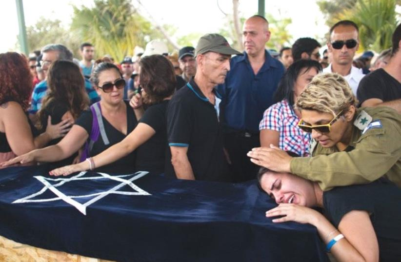 Relatives of Daniel Tregerman, a four-year-old killed in a 2014 mortar attack, mourn during his funeral near the border with the Gaza Strip (photo credit: REUTERS/Ronen Zvulun)