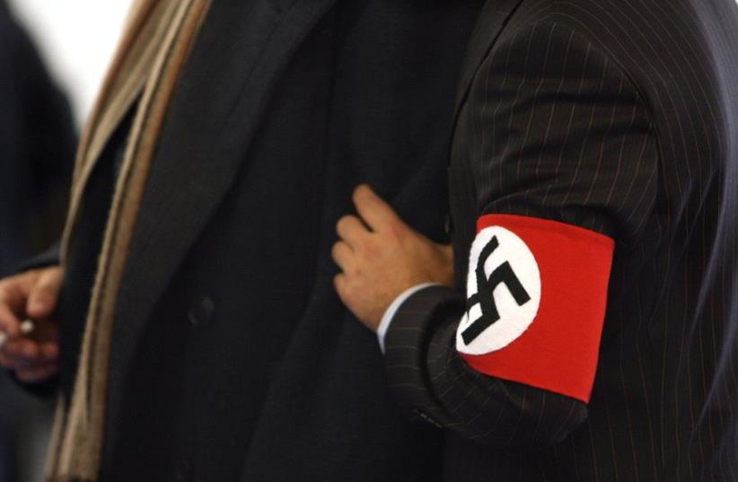A man wears a costume with a swastika armband  (photo credit: REUTERS)