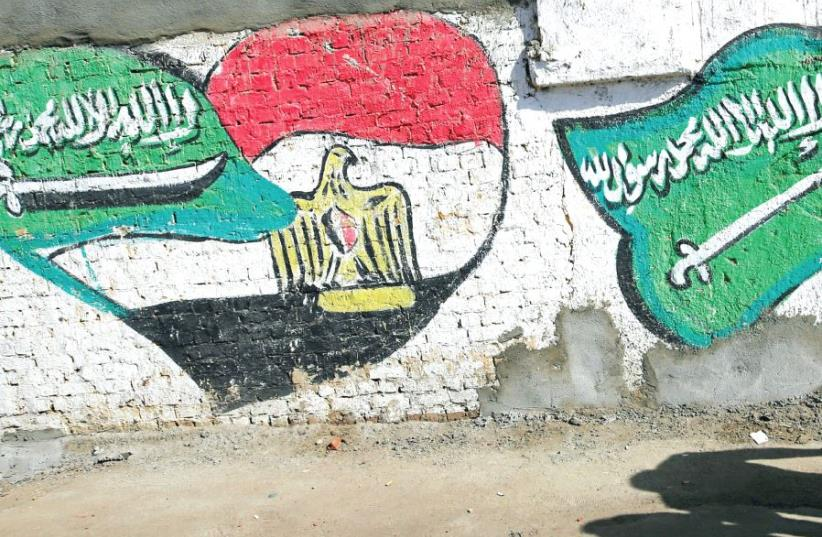THE SHADOWS of men walking are seen in front of graffiti depicting relations between Egypt and Saudi Arabia in Cairo last year (photo credit: REUTERS)